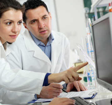 Scientists working on computer in laboratory.